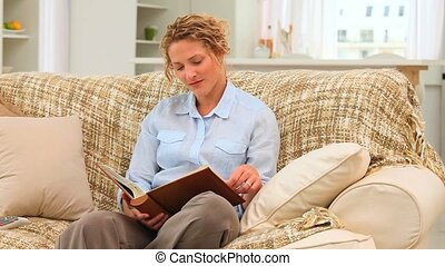 Casual curly haired woman looking at an album on her sofa