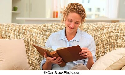 Relaxed woman looking at an album on the sofa