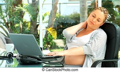 Tired pregnant woman working on a laptop