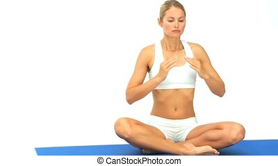 Pretty blonde woman in yoga position on a blue ground cloth
