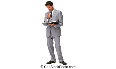 Elegant businessman standing up with a notebook isolated on...