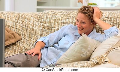 Curly-haired woman laughing in front of her tv on her couch