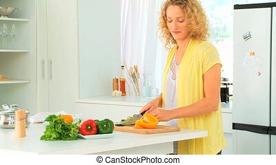 Curly haired woman cooking in her kitchen