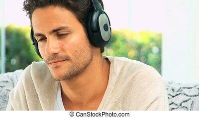 Handsome dark haired man listening to music with headphones...