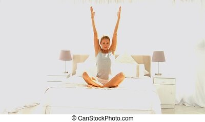 Cute lady doing yoga on her bed