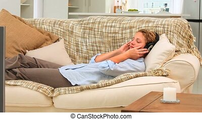 Elongated woman listening to music on the couch