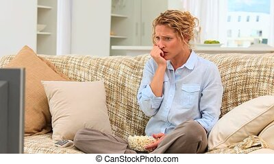 Curly haired woman watching a scary movie in her living room