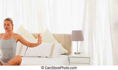 Casual girl doing exercises of relaxation on her bed