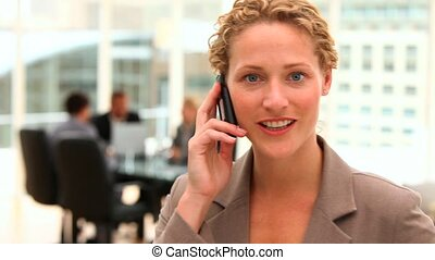 Blonde business woman talking on th