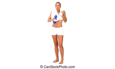 Blonde woman after sports with a flask and towel against a...