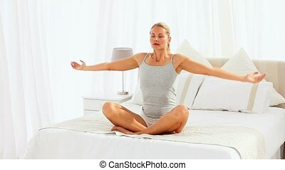 Woman in lotus position sitting on her bed