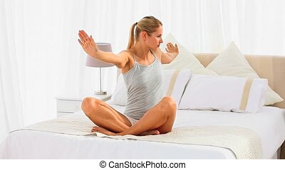 Blonde woman sitting on her bed doing some exercises