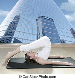 black mat yoga woman window view city urban buildings -...