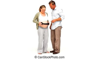 Pregnant woman with headphones on her belly dancing with her...