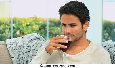 Handsome man savouring a glass of r