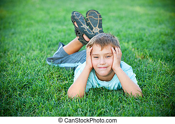 Funny boy lying on the green grass - A cheerful kid is lying...