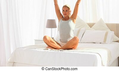 Good looking woman on her bed doing yoga