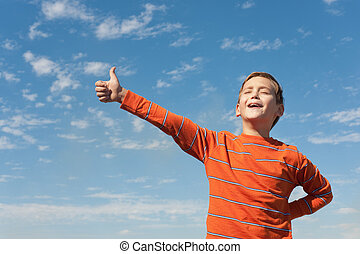 Singing happy boy in front of the sky - A happy kid is...