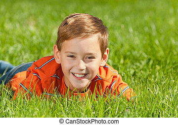 Laughing boy on the grass - A portrait of a cheerful kid...