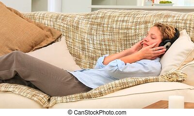 Curly blonde woman listening to music on her sofa