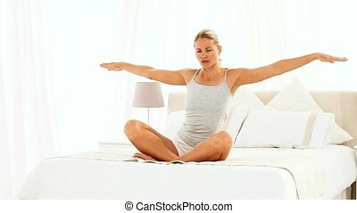 Blonde woman sitting on her bed