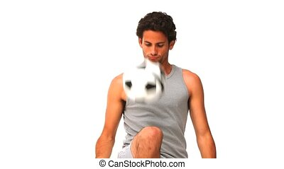 Casual man playing soccer against a white background
