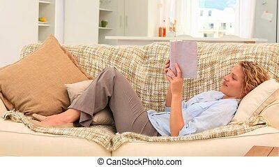 Casual woman reading a book on her sofa