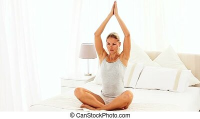 Woman doing the lotus position sitting on her bed