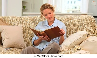 Cute woman looking at an album on her sofa