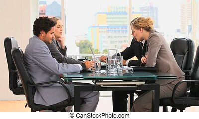 Four people during a business meeting at the desk