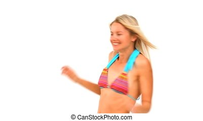Blonde woman in swimsuit playing with a frisby against a...