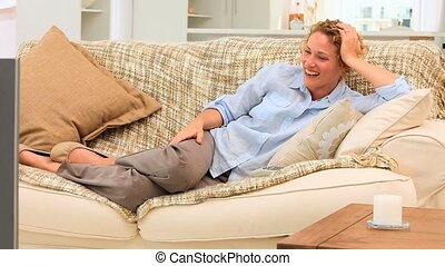 Casual woman laughing in front of her tv in the living room