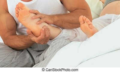 Attentive man massaging feets wife in the bedroom