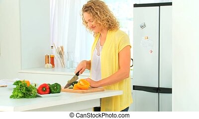 Curlyt haired woman preparing the dinner in the kitchen