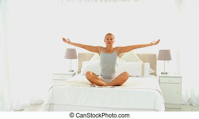 Blonde woman doing the lotus position on her be