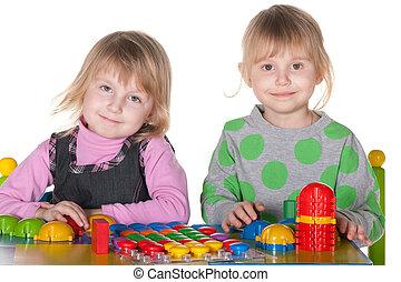 Two smiling girls playing vivid toys