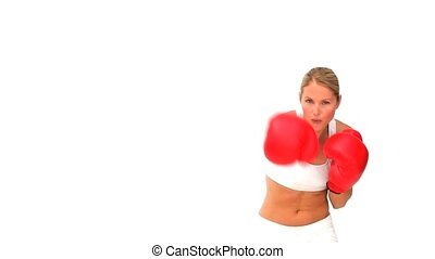 Dynamic blonde woman with red boxing gloves against a white...