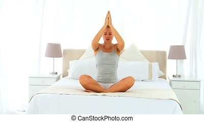 Woman doing yoga on her bed
