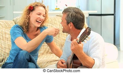 Engaging man playing guitar with his wife on the sofa