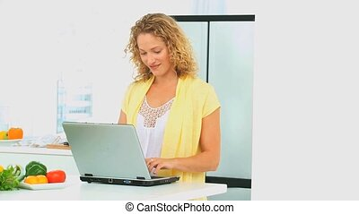 Curly haired woman looking at a recipe on her laptop in the...