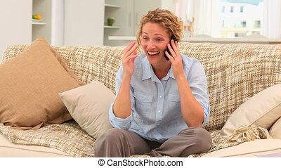 Casual woman laughing on the phone in the living room