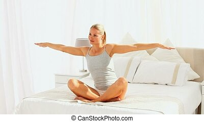 Woman doing exercises of relaxation in her bedroom