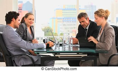 Meeting between four business people at a desk