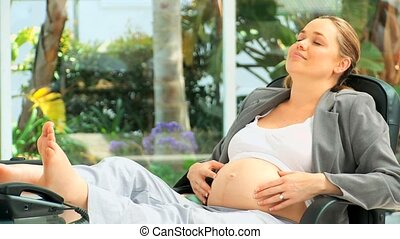 Pregnant business woman having a rest at her desk