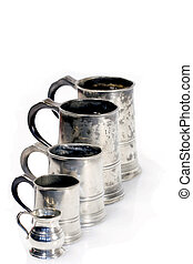 Diagonal line of pewter mugs and a measure isolated on white...