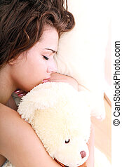 Beautiful woman sleeping with the toy bear