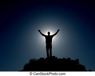 Hallelujah - Silhouette of man on a summit with upraised...