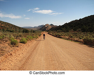 backroad bicycling - a woman bicycles along a dirt road in...