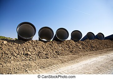 pipelines on the mud - group of black big pipelines at the...