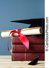 Graduation Mortarboard, Scroll and Books - A stack of old,...